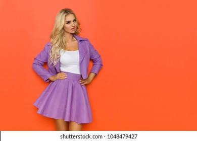 Beautiful blond woman in violet mini skirt and jacket is posing with hands on hip and looking at camer. Three quarter length studio shot on orange background.
