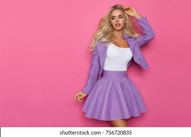 Beautiful blond woman in violet mini skirt and jacket is posing with hand in hair and looking away. Three quarter length studio shot on pink background.