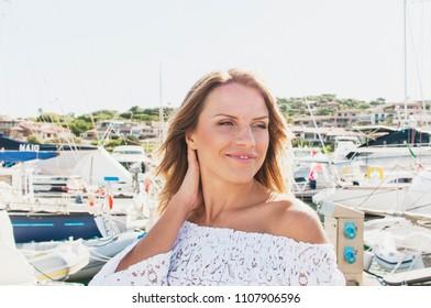 Beautiful blond woman walking in summer harbor