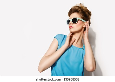Beautiful blond woman wearing blue and brown dress and glasses