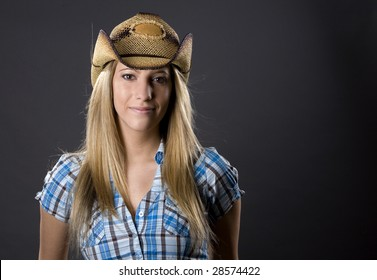 beautiful blond woman wearing cowboy outfit on grey