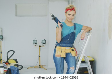 Beautiful blond young female in jeans overalls and red headband standing relaxed leaning on stepladder holding electric drill and looking at camera smiling with unpainted wall and workbench nearby.
