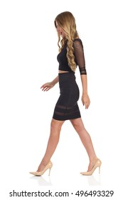 Beautiful blond young woman in black dress and beige high heels walking. Side view. Full length studio shot isolated on white.