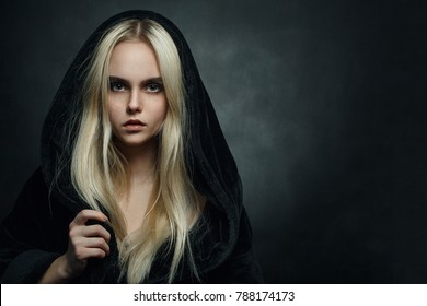 beautiful blond young woman in black hood looking at camera