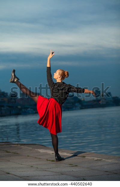 Beautiful blond young woman with black and red costume doing the splits near water.