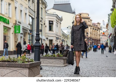 Beautiful blond young woman dressed in a coat walking down the street of the old town center
