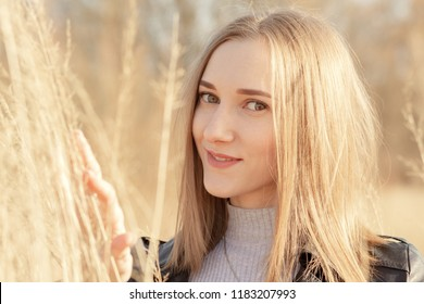 beautiful blond young woman at dry grass looking at camera, smiling