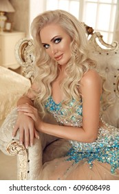 Beautiful blond young woman in fashion dress sitting in royal armchair in luxury modern interior. Beauty style indoors photo portrait.