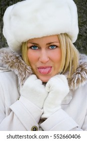 Beautiful Blond Young Woman Girl in White Fake Fur Hat and Coat Sticking Out her Tongue