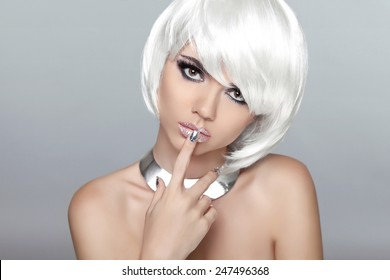 Beautiful blond young woman with polish finger. Makeup. Manicured nails. Studio photo. Girl with white Short Hair.