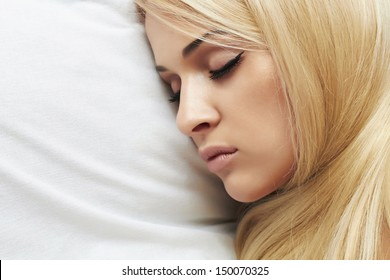 Beautiful blond young woman sleeping on the bed. beauty woman. white pillow. sweet dreams