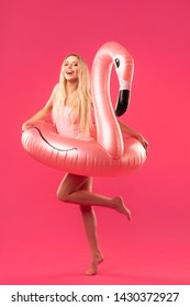 beautiful blonde in a bathing suit with an inflatable flamingo on a pink background