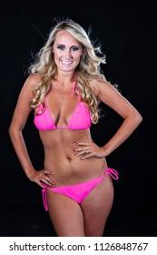 A beautiful blonde bikini model posing in a studio environment