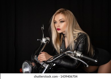 beautiful blonde in a black leather jacket sitting on a motorcycle.