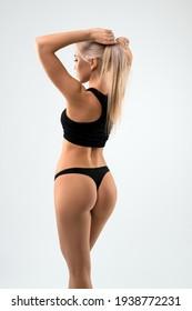 Beautiful blonde in black lingerie rearview