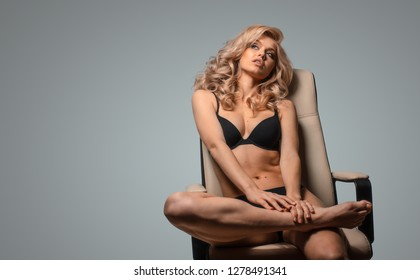 Beautiful blonde in black underwear sitting on a chair thinking about something