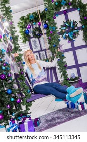 beautiful blonde in blue pants sitting on a swing in the New Year's decorations on the white terrace and okruzhienii Christmas balls and Christmas tree holding gifts.