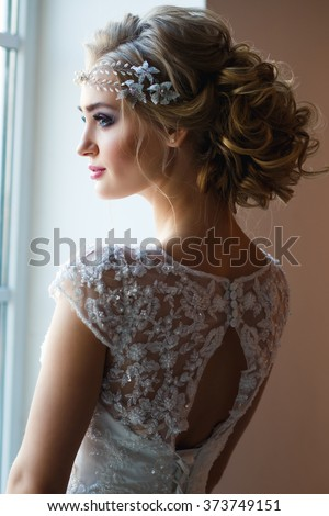 Beautiful blonde bride in gorgeous luxury dress in a loft space in a morning. Modern wedding photo