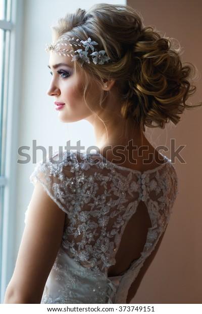 Beautiful blonde bride in gorgeous luxury dress in a loft space in a morning. Modern wedding photo