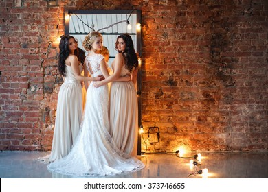 Beautiful blonde bride in luxury wedding dress and pretty twins bridesmaids in similar dresses in a morning in a loft space with a mirror and garland of lamps. Fashion modern wedding photo