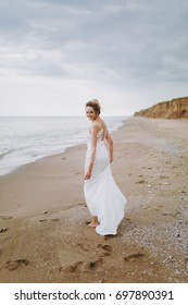 The beautiful blonde bride on a walk by the sea