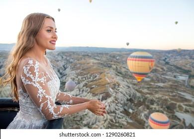 Beautiful blonde bride posing in hot air balloon in Cappadocia, Turkey