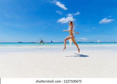 Beautiful blonde bride in a white bikini and a veil having fun on the beach. Tropical sea in the background. Summer vacation concept.