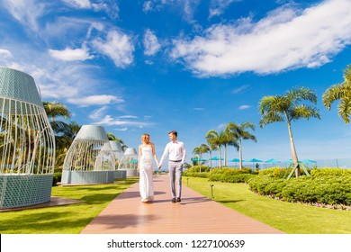 Beautiful blonde bride in white wedding dress and the groom on the roof of the hotel. Tropical sea and palm trees in the background. Summer vacation concept.