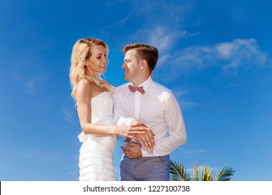 Beautiful blonde bride in white wedding dress and groom hands showing wedding rings. Tropical skies and palm trees in the background. Summer vacation concept.