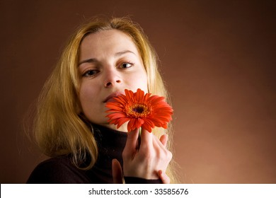A beautiful blonde in brown jumper posing with a red flower on a dark background