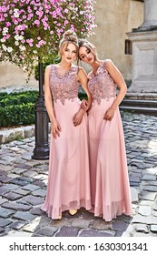 Beautiful blonde and brunette bridesmaids with luxury hairdo in gorgeous elegant stylish pale pink floor length v neck chiffon gown dress decorated with sequins sparkles and rhinestones on flowers