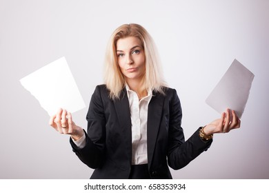Beautiful blonde business woman in black jacket rends piece of paper. Breaking contract concept.