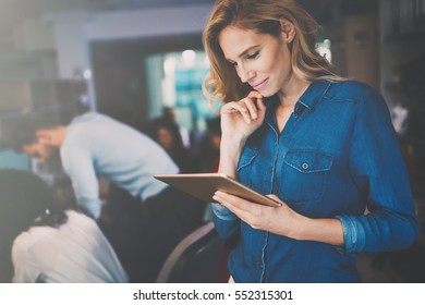 Beautiful blonde businesswoman holding tablet in modern office