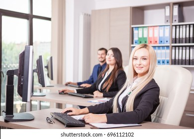 Beautiful blonde businesswoman in the office in front of her team next to colleagues