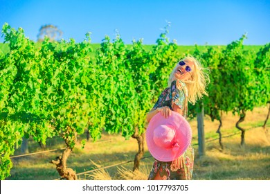 Beautiful blonde carefree woman with hat walks near the vineyards. Happy woman enjoying during a popular wine tasting tour in the wine region of Margaret River, Western Australia.