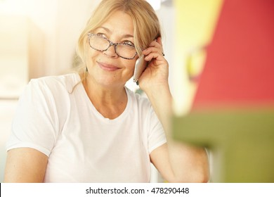 Beautiful blonde Caucasian elderly female wearing glasses having phone conversation with her old friend using electronic device, discussing latest news with cute smile on her face, sitting at home