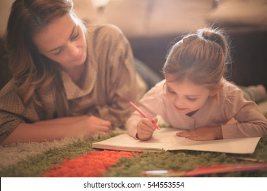 Beautiful blonde Caucasian girl lying on the floor with her mother and drawing.