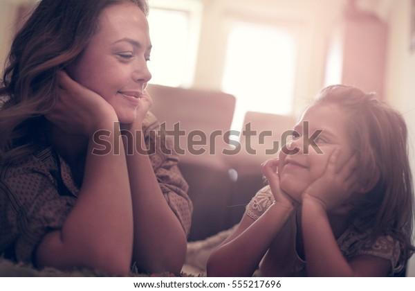 Bella bionda caucasica ragazza sdraiata sul pavimento con la madre e sorridente.