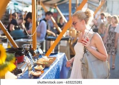 Beautiful blonde caucasian lady wearing white summer dress buying freshly prepared meal at a local street food festival. Urban international kitchen event in Ljubljana, Slovenia, in summertime.