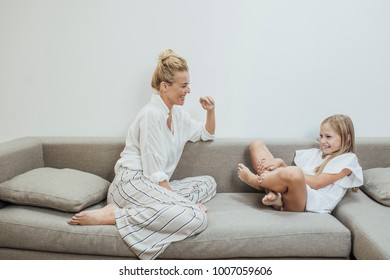 Beautiful blonde Caucasian smiling woman enjoying time at home with her cute daughter.