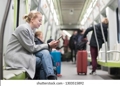 Beautiful blonde caucasian woman wearing winter coat reading on the phone while traveling by metro. Public transportation concept.