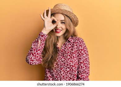 Beautiful blonde caucasian woman wearing summer hat doing ok gesture with hand smiling, eye looking through fingers with happy face.