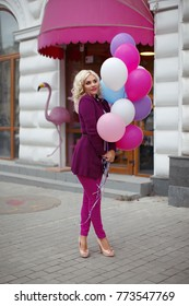 beautiful blonde celebrating a holiday and walking around the city with balloons