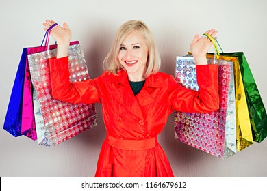 beautiful blonde cheerful woman shopaholic in a green dress with shopping bags on a gray background . concept of shopaholism and sales