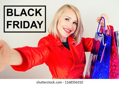 beautiful blonde cheerful woman shopaholic taking pictures of herself selfie on the phone with shopping bags on a gray background . concept of shopaholism and black friday sales