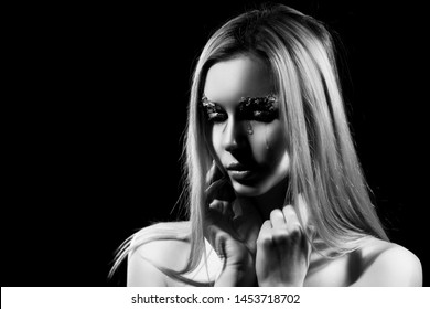 Beautiful blonde is crying, covering her topless big breasts with her hands. Tears on her face. Avant-garde makeup, eyebrows made of foil. Dark background. Conceptual artistic black and white photo.