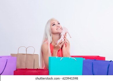 Beautiful blonde to do shopping. Girl or women with colored shopping bag. Success shopping. Select clothes. Surprised and funny girl with shopping packet and new shoes