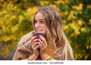 beautiful blonde is drinking coffee in the autumn park