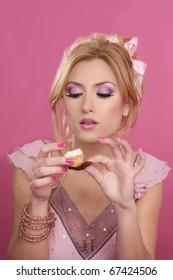 beautiful blonde eating diet sweet on pink background
