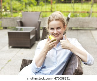 Beautiful blonde eating a pear. Young smiling girl sitting on the terrace. Beautiful woman in a blue shirt. A young girl lead a healthy lifestyle